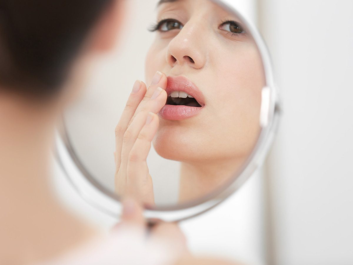 Woman with a cold sore looks in the mirror and touches her mouth