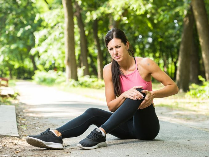 natural home remedies muscle cramps, woman running at the park having a muscle cramp