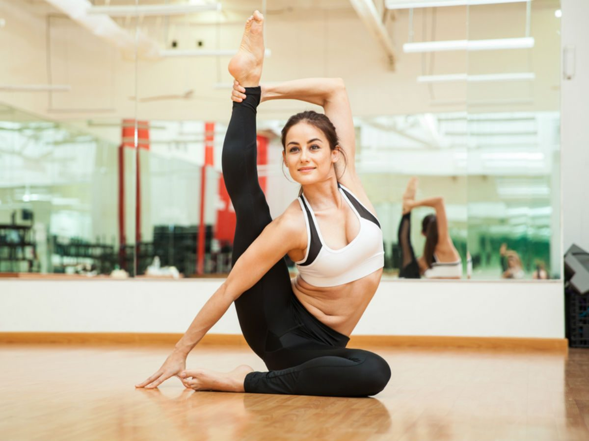 be more flexible, woman doing a high leg yoga pose