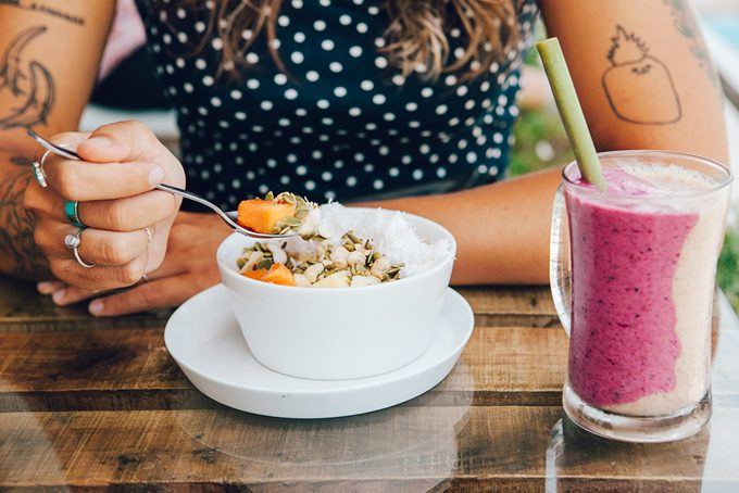 woman eating breakfast bowl _ when eat for weight loss