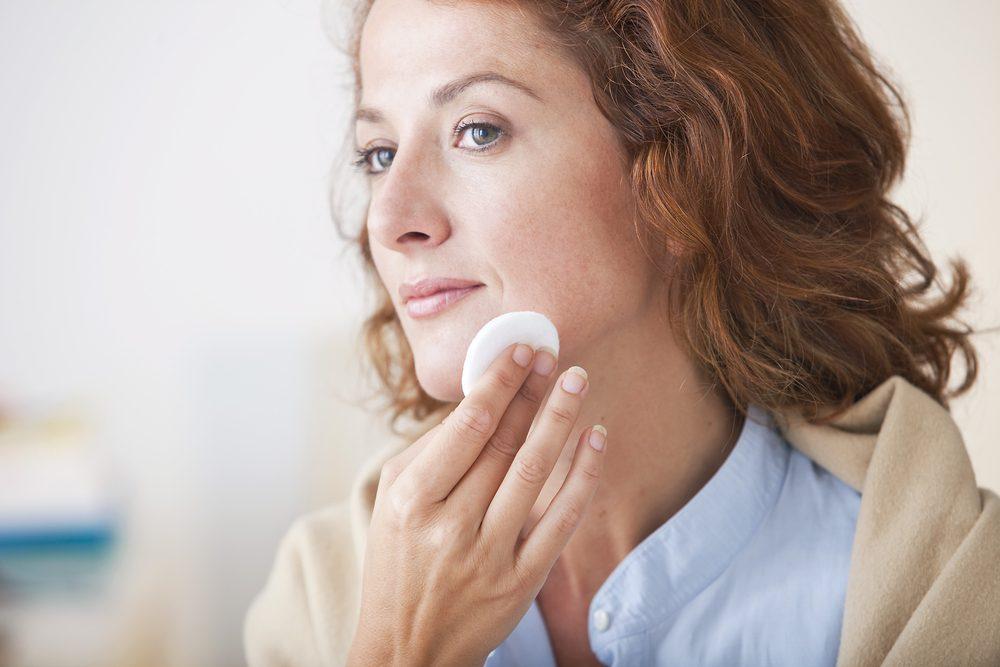 mulher removendo maquiagem