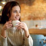Caffeine, smiling woman drinking coffee