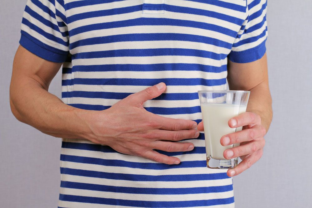 Lactose intolerant man holds his stomach and a glass of milk