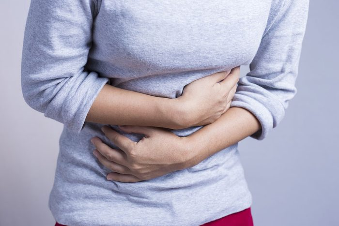 Lactose intolerant woman holds her stomach in pain