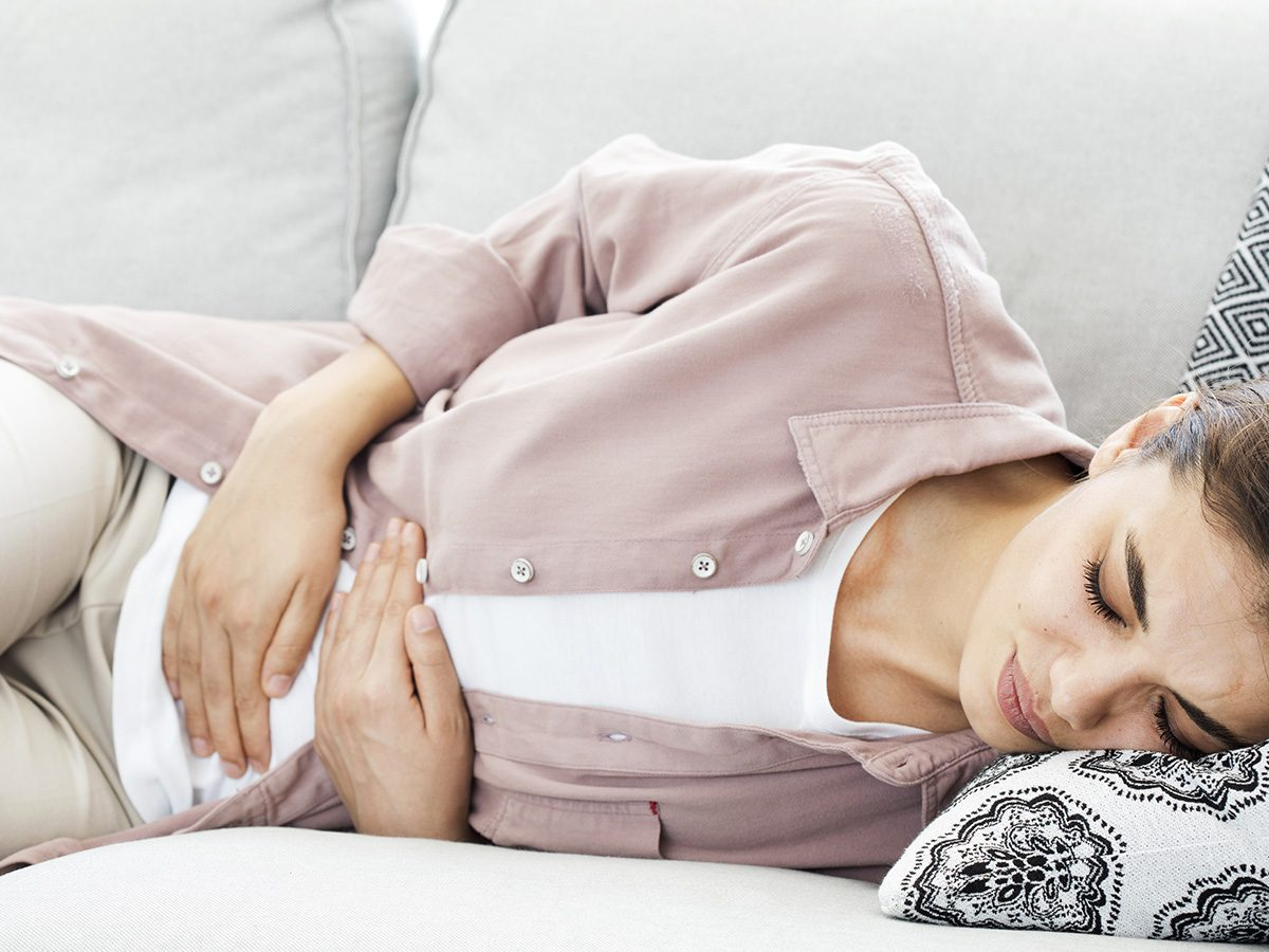 Gynecologist, woman with menstrual cramps clutching stomach