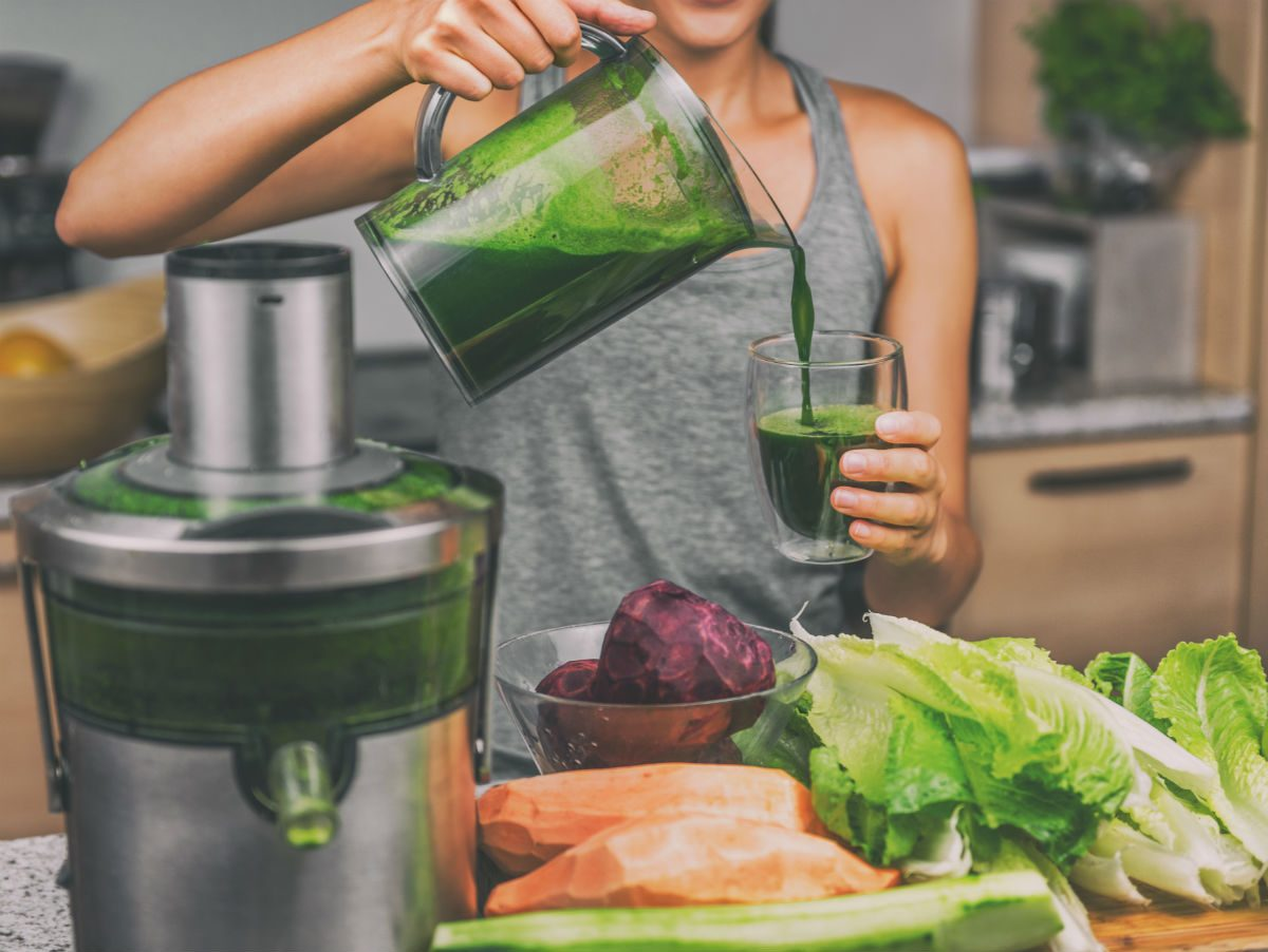 how to juice, woman with a juicing machine making green juice