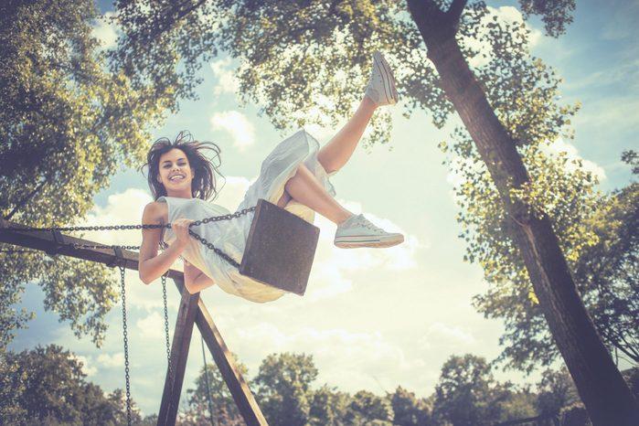Happy young woman having fun on the swing
