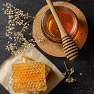 Honey,bee,and,honeycomb,with,honey,dipper,and,dry,flower