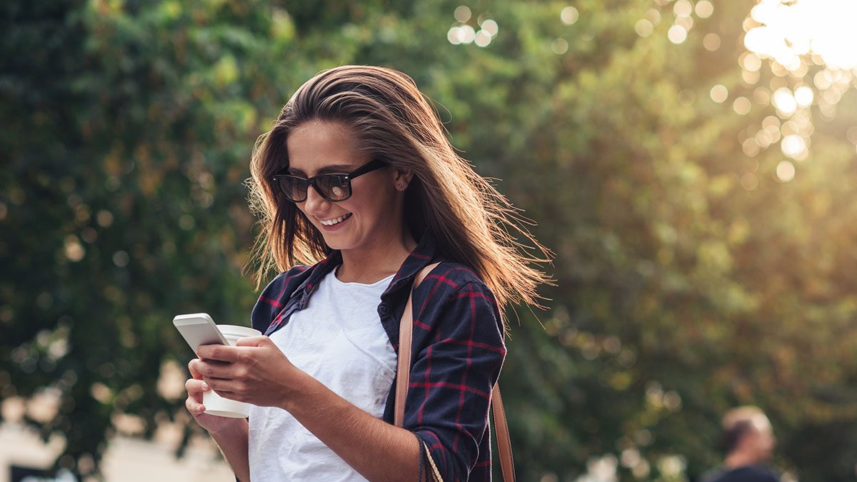 Texting, woman walking with smartphone