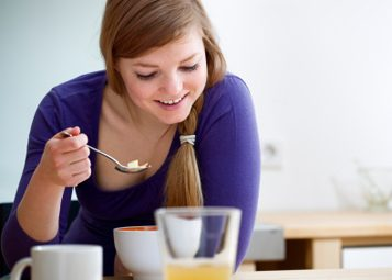 woman eating cereal breakfast