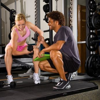 woman and man at the gym personal trainer weights