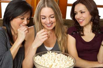 women snacking on popcorn