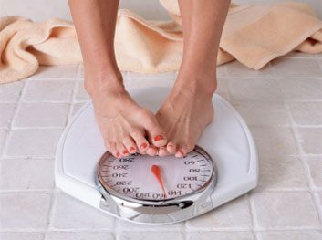 woman on scale weight loss diet