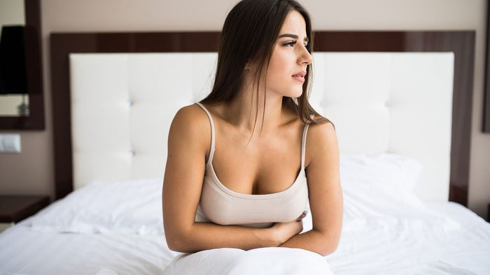 woman on bed holding belly