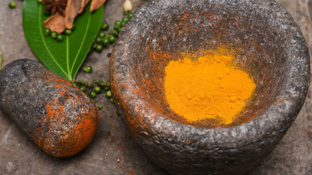 turmeric being crushed with mortar and pestle