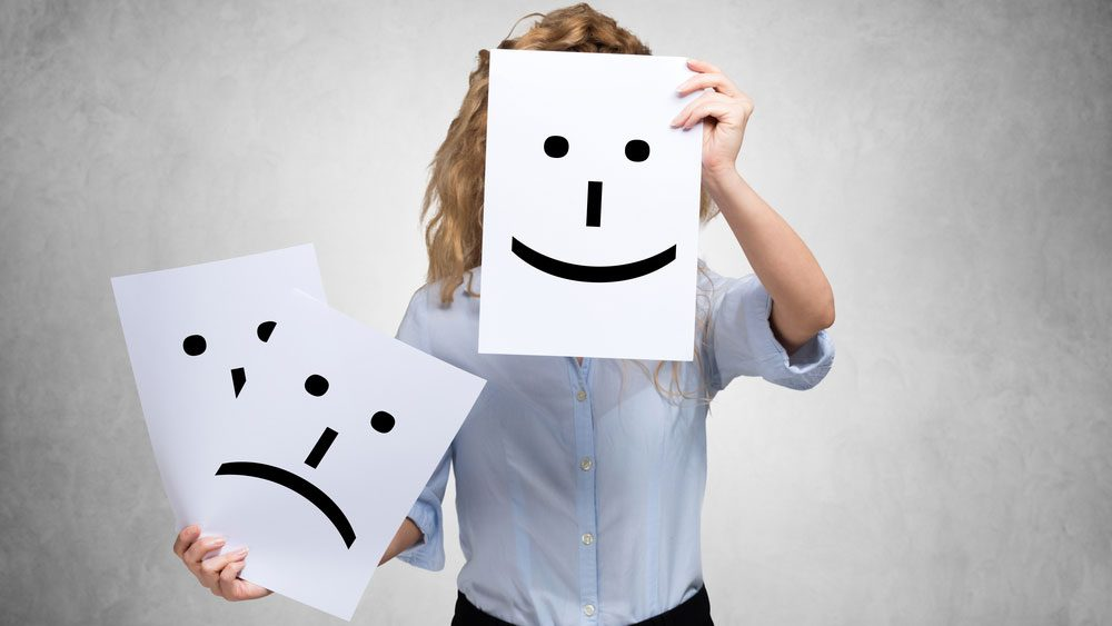 woman holding emoji faces of happy and sad
