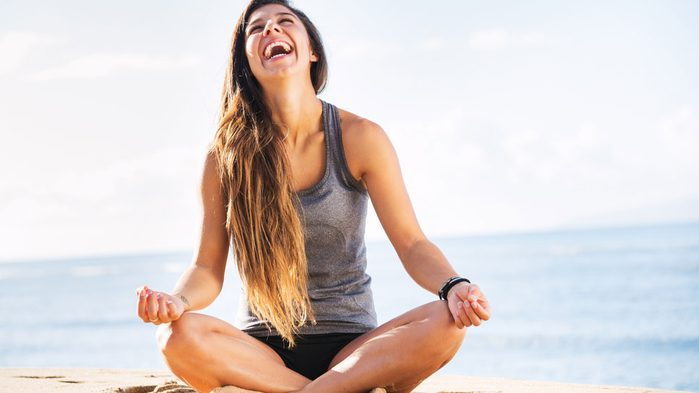 fit woman laughing on the beach