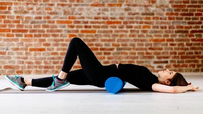 woman using a foam roller on her lower back