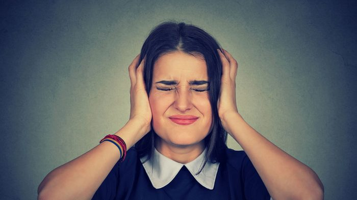 can't stand the noise_ frustrated woman covers her ears