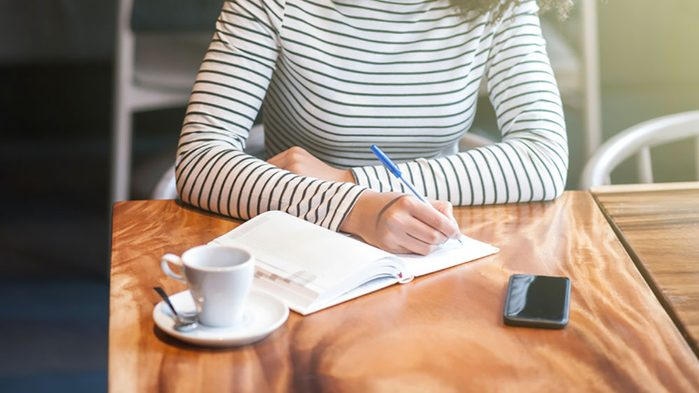 woman journaling at a coffee shop
