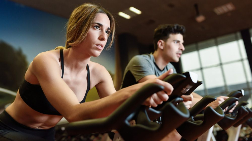 spinning mistakes: Woman in a spin class wondering if she's burning enough calories