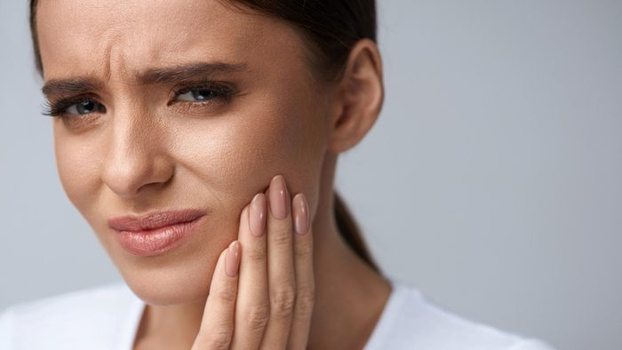 woman who is wincing with pain from a toothache