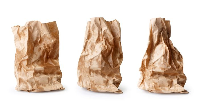Three greasy, but mouth-watering paper bags with hopefully cronut burgers inside