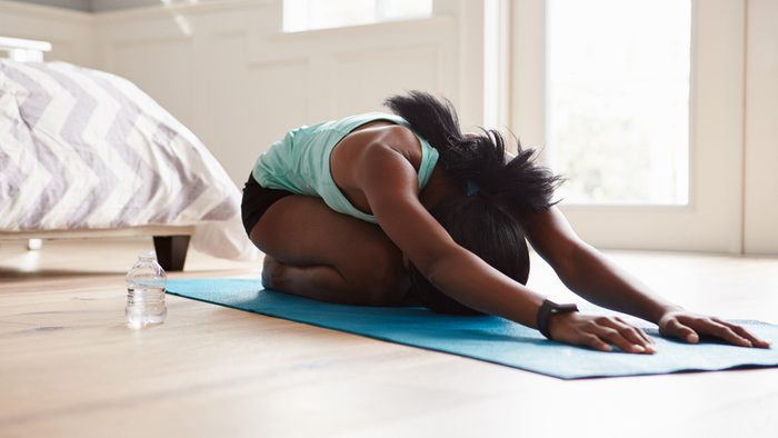Exercise Prescription for anxiety, stress and depression: woman in cat pose doing yoga