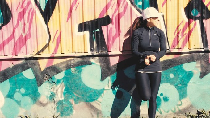 AS and exercise, Naomi Ban in workout gear standing near a graffiti wall