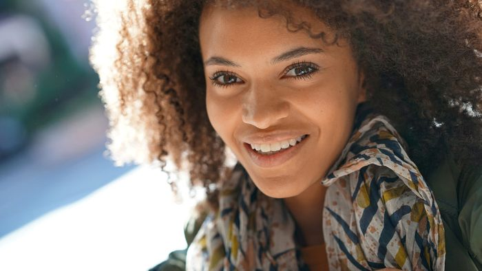 Skin fix for adult acne, a woman with glowy skin smiling