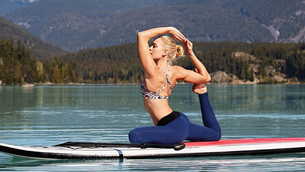 Summer 2017 Fitness Fashion, a woman on a paddle board doing yoga