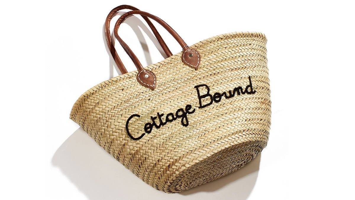 "summer layering tote, a straw bag with ""cottage bound"" written on the front"