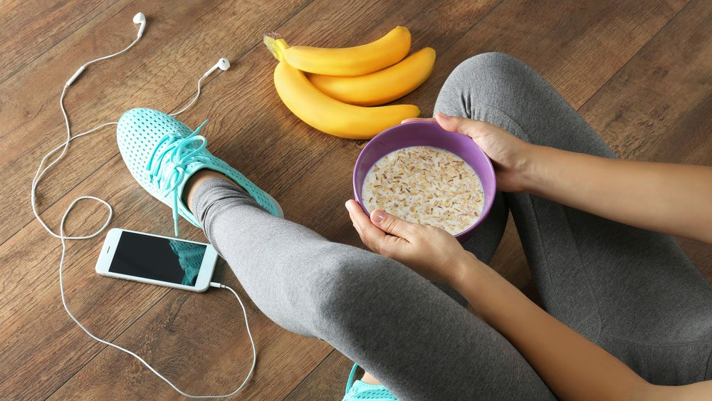 eat after a run, a woman sitting on the floor with some food after a run