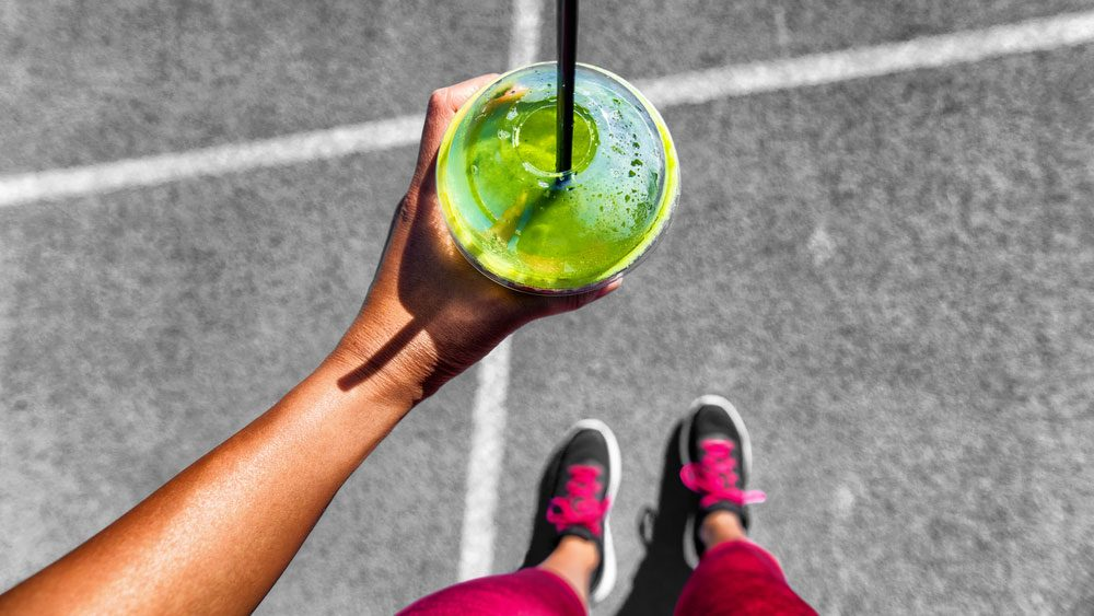 "What to eat before a run, a woman doing a ""from where I stand"" selfie showing running shoes and a green smoothie"