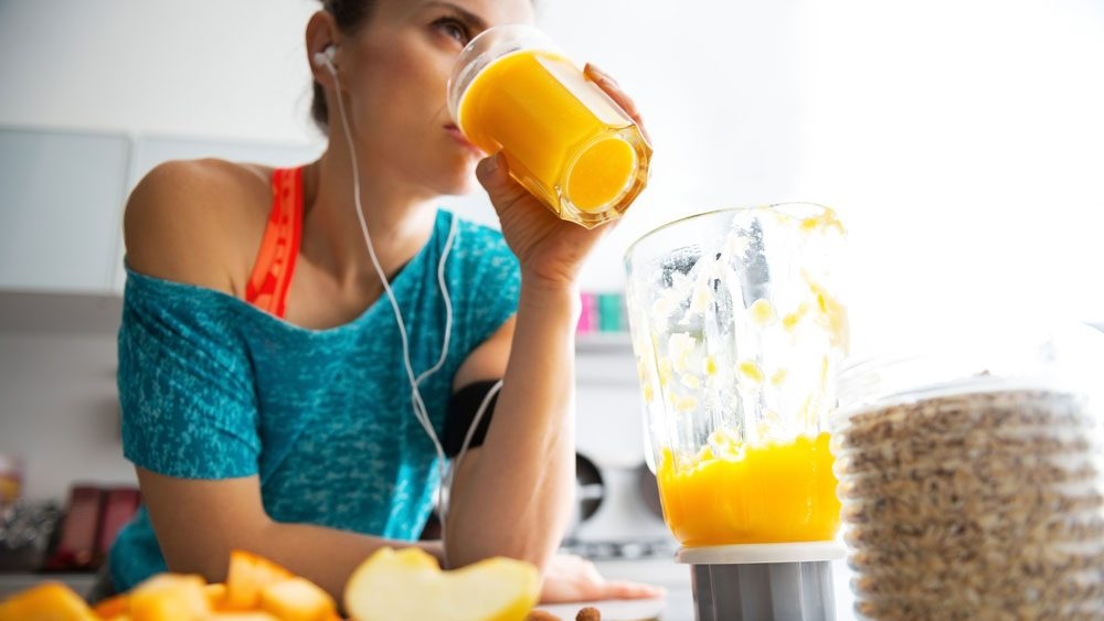 eat for running, a fit woman in her kitchen drinking a peach smoothie