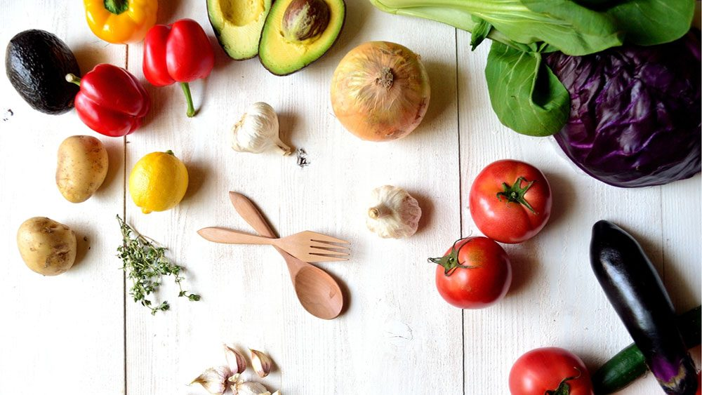 foods for a healthier heart, bright coloured veggies on a white cutting board