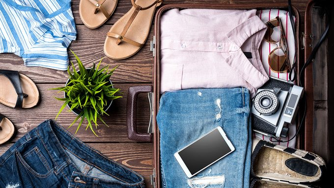 covered for health insurance, a suitcase with women's clothing and belongings ready for travel