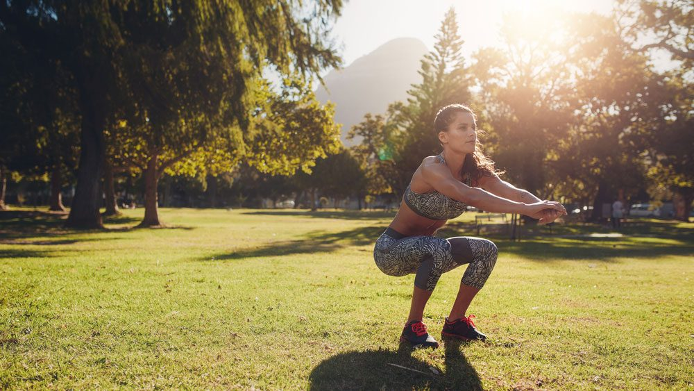 staying motivated in summer outdoor workout, woman doing squats in the park