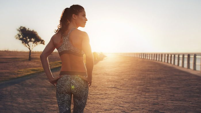 staying motivated in the summer, a woman on a beach in workout gear