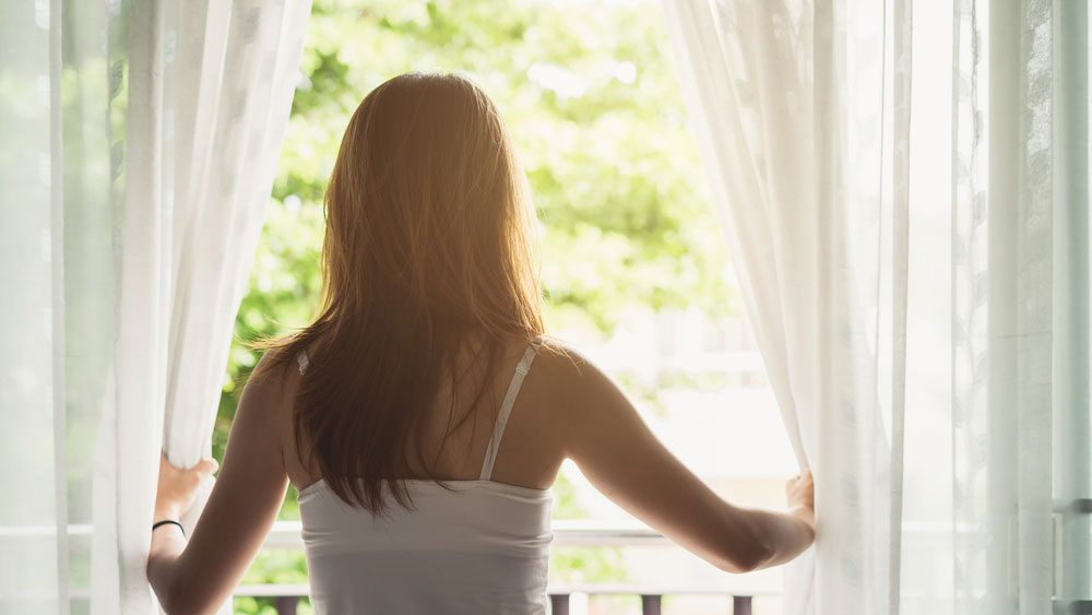 home giving you anxiety breathing space, a woman opening sheer drapes
