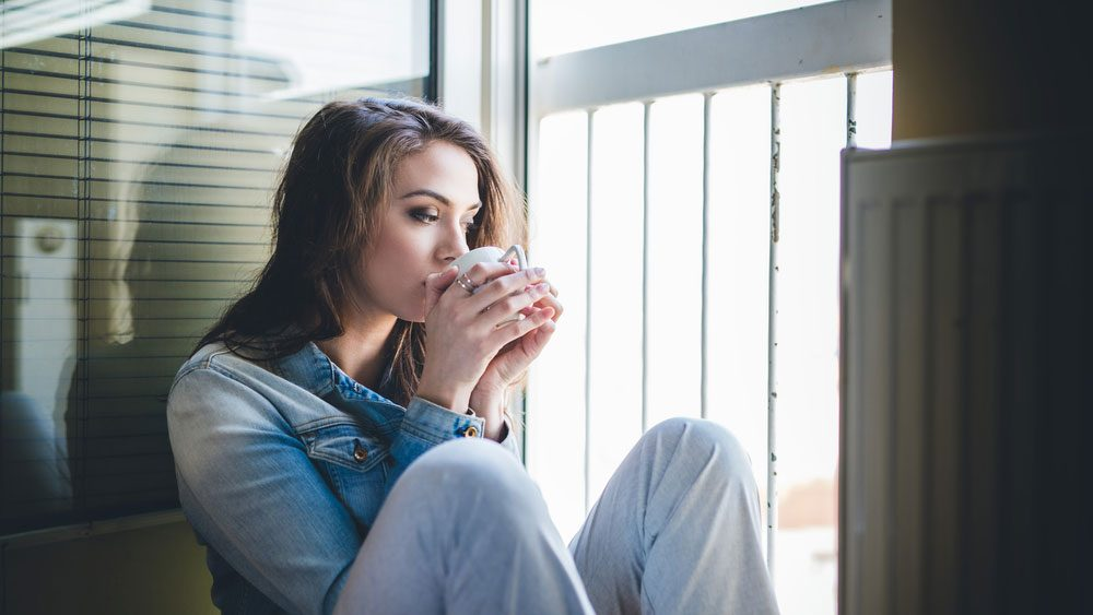 home giving you anxiety, woman drinking coffee on her balcony