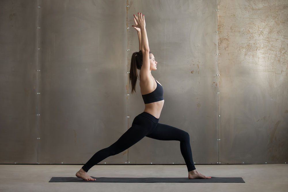 Stretching for stiffness, a woman in Warrior I