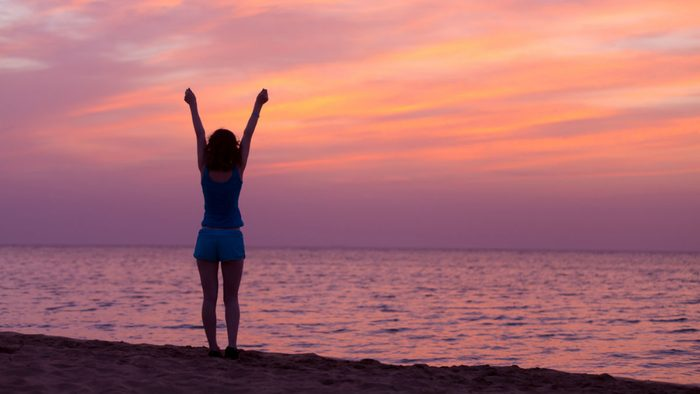 wellness getaways feel good, woman on a beach at sunrise, loving life