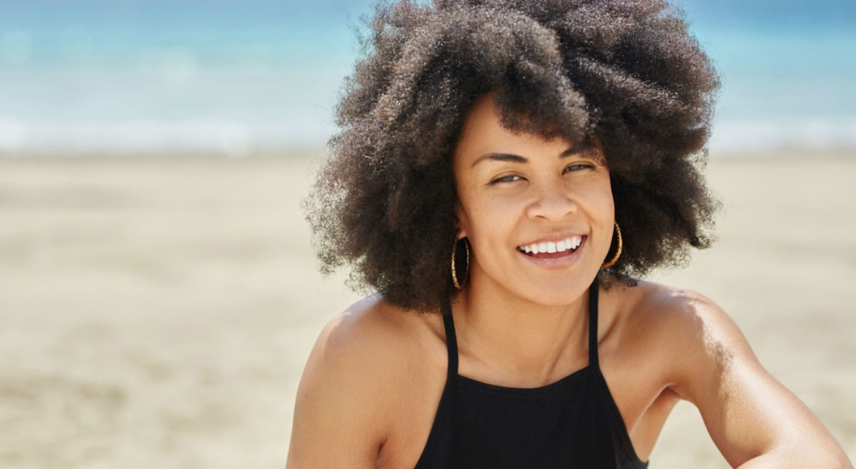 wellness getaways joy, woman smiling on the beach
