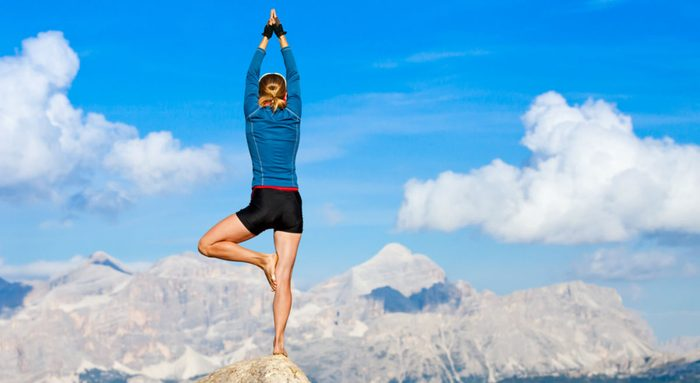 wellness getaways, a woman doing a balance yoga pose on a mountain