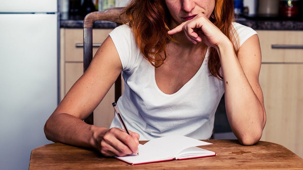 Thanksgiving food prep, woman writing her list of groceries