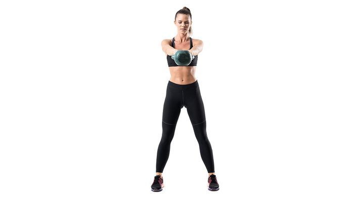 best kettlebell moves for abs, woman with a toned stomach holding a kettlebell at the top of a swing