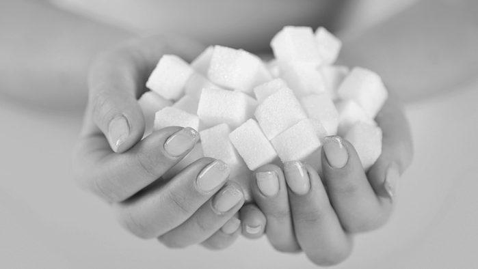 Cut back on sugar, woman holding sugar cubes