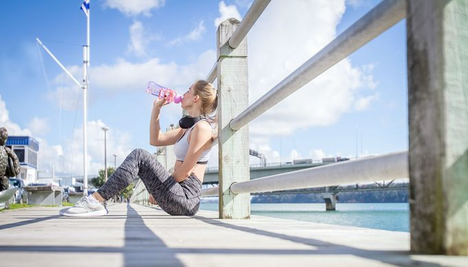 drink water for weight loss, woman drinking water during a run