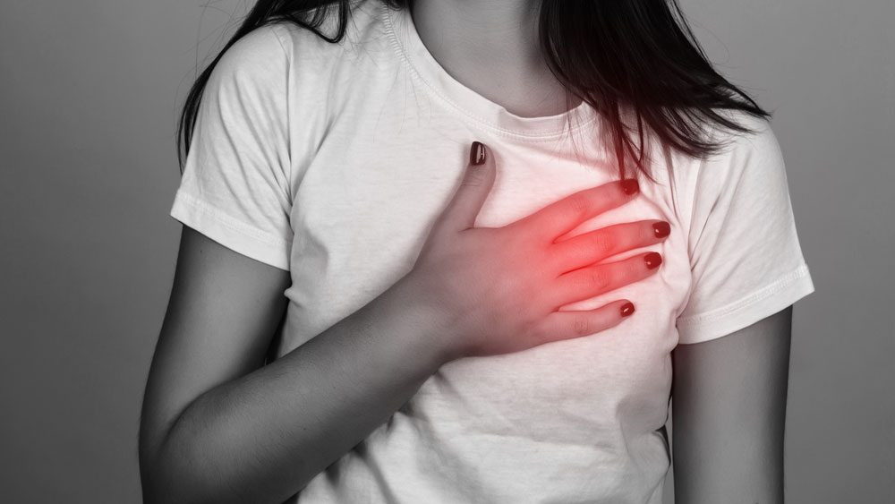 heart attack symptoms for women, a young woman holding her chest